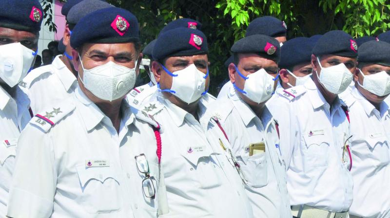 Traffic policemen wear masks during a campaign in New Delhi.