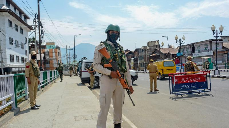 A CRPF jawan stands guard along a street on the first day of the two-day curfew in Srinagar. PTI Photo