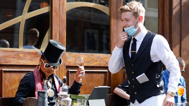 A waiter wearing a face mask or covering due to the COVID-19 pandemic, passes a customer drinking outside a restaurant in London. AFP Photo