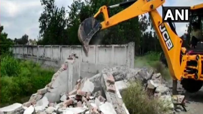 'The irrigation department along with the district administration demolished the wall today which was erected illegally,' official said. (Photo: ANI)