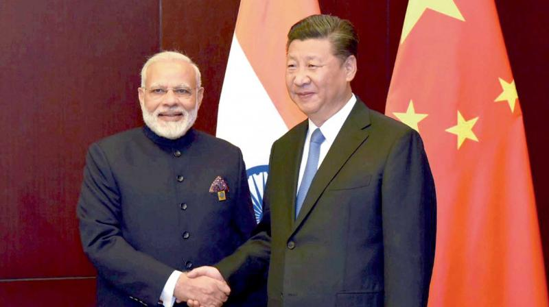 Prime Minister Narendra Modi and China's President Xi Jinping shake hands as they pose for a photo during a meeting on the sidelines of the Brics Summit in Xiamen in on September 5. (Photo: PTI)