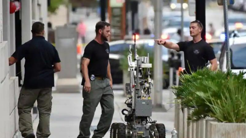 Bomb squad police prepare a robot to enter a parking garage a block away from the scene of a multiple shooting at the Jacksonville Landing on Sunday. (Photo: AP)
