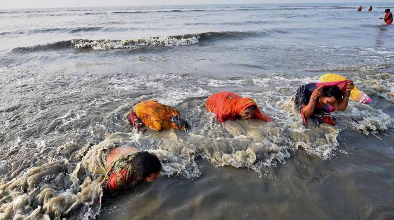Sagar Island: Devotees take holy dip at the sea shore of Gangasagar Island on Friday. Sadhus and devotees have gathered at Gangasagar for 'holy dip' on the occasion of Makar Sankranti festival. (Photo: PTI)