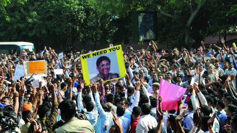 Delhi police personnel display pictures of former IPS officer Kiran Bedi during a protest on Tuesday.  (Photo: Biplab Banerjee)