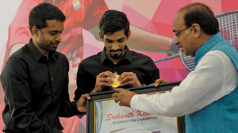 Ace shuttler Kidambi Srikanth (centre) with coach Pullela Gopichand (left) at a felicitation function in New Delhi. (Photo: Sondeep Shankar)