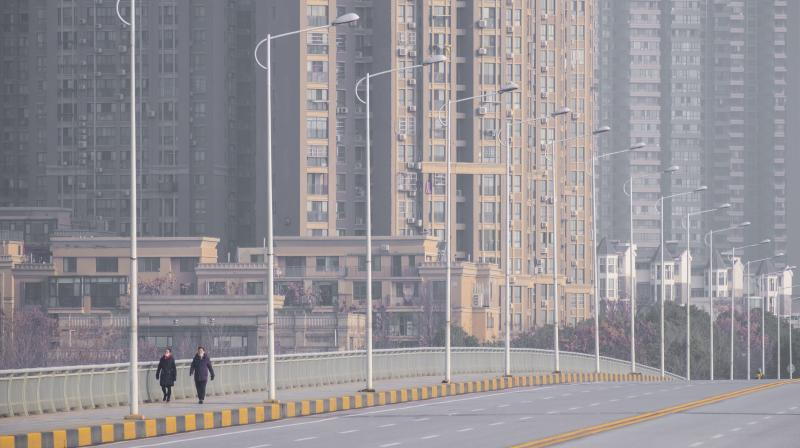 People wearing face masks walk down a deserted street in Wuhan in central China's Hubei Province, Tuesday, Jan. 28, 2020. China's death toll from a new viral disease that is causing mounting global concern rose by 25 to at least 106 on Tuesday. (AP)