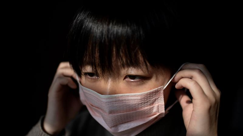 26-year-old Wuhan native Lucy Huang, a documentary film-maker living in Beijing, puts on a protective facemask at her house in Beijing. Wuhan natives are being subjected to community checks bordering on stigma. (AFP)