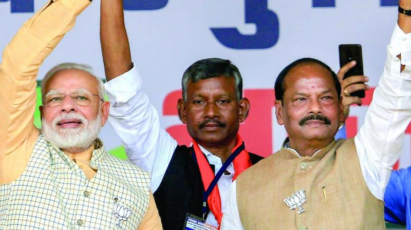 Prime Minister Narendra Modi with Jharkhand chief minister Raghubar Das waves at supporters during an election rally in Jamshedpur on Tuesday. (Photo: PTI)