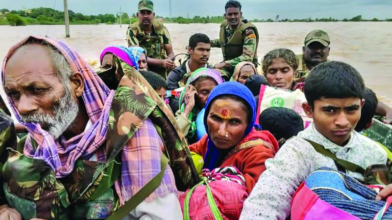 Army personnel carry out a rescue operation in a  flood-affected area in Belgaum district on Friday. (Photo: PTI)