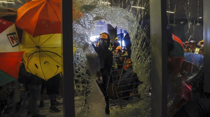 A small group, mostly students wearing hard hats and masks, used a metal trolley, poles and pieces of scaffolding to hack through reinforced glass and charge at the government compound. (Photo: AP)