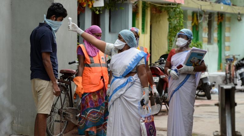 An Accredited Social Health Activists (ASHA) worker (L) checks the temperature of Greater Hyderabad Municipal Corporation (GHMC) municipal worker outside a containment zone in Hyderabad. PTI Photo