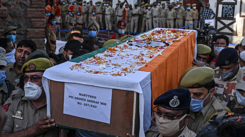 Police personnel carry the coffin of a police officer who died during an attack on Indian security personnel by suspected militants in downtown Srinagar, at the police headquarters in Srinagar on September 12, 2021. (TAUSEEF MUSTAFA / AFP)