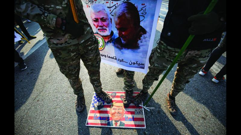 Members of the Hashed al-Shaabi paramilitary force step on a makeshift US flag with a caricature of President Donald Trump during the funeral procession of Iraqi  paramilitary chief Abu Mahdi al-Muhandis (poster left) and Iranian military commander Qasem Soleimani (poster right) in Baghdad. (Photo: AFP)