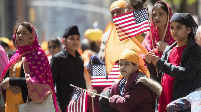 A Sikh American family watches participants march down Madison Avenue during the Sikh Day Parade. (Photo: AP)
