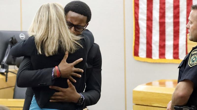 Botham Jean's younger brother Brandt Jean hugs convicted murderer and former Dallas Police Officer Amber Guyger after delivering his impact statement to her after she was sentenced to 10 years in jail, Wednesday. (Photo: AP)