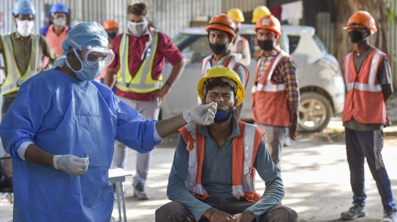 A health worker takes sample from a construction worker for COVID-19 test as others wait for their turn, in New Delhi. — PTI photo