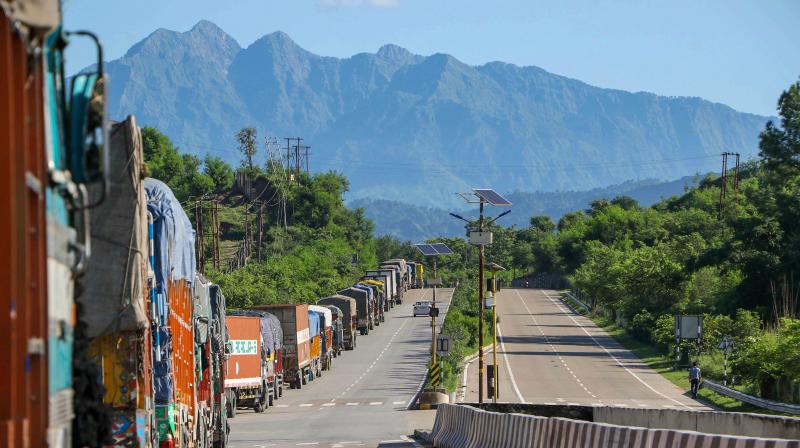 Trucks wait for the opening of Jammu-Srinagar national highway, on the outskirts of Jammu. — PTI photo