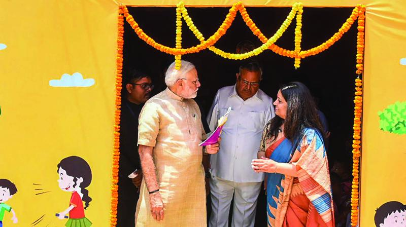 Prime Minister Narendra Modi visits an anganwadi centre in Bijapur, Chhattisgarh, on April 14. State chief minister Raman Singh is also seen. (Photo:PTI)
