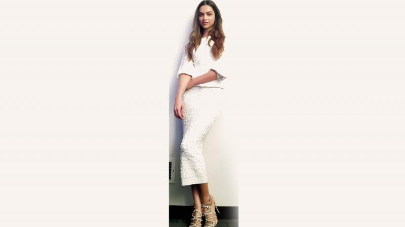 Deepika Padukone rocks an all-white ensemble and accents them with strappy beige-gold heels.