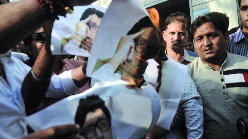 Congress party workers burnt posters of MNS chief Raj Thackeray at Azad Maidan. (Photo: Shripad Naik)