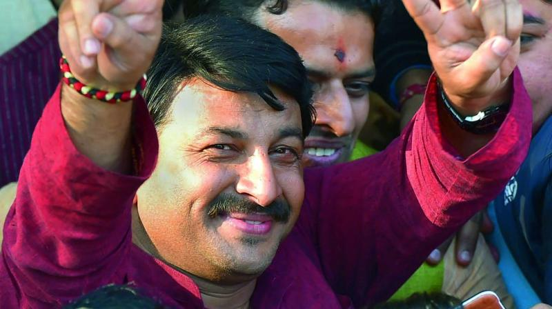 Delhi BJP president Manoj Tiwari flashes a victory sign on his arrival at the party headquarters in New Delhi. (Photo: PTI)