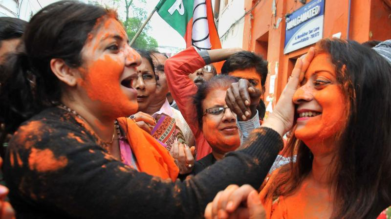Actress-turned-BJP Mahila Morcha president Locket Chatterjee (left) and party workers celebrate the party's victory in Gujarat and Himachal Pradesh Assembly elections, outside the state party headquarters in Kolkata. (Photo: PTI)