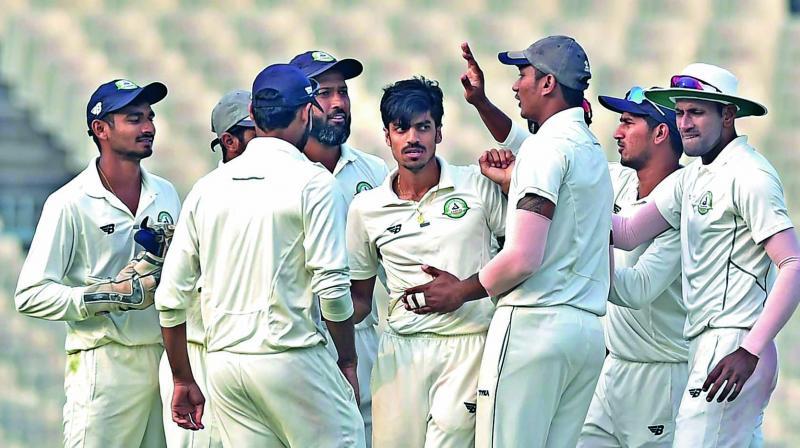 Vidarbha bowler Rajneesh Gurbani celebrates the fall of a Karnataka wicket with his team mates. (Photo: PTI)