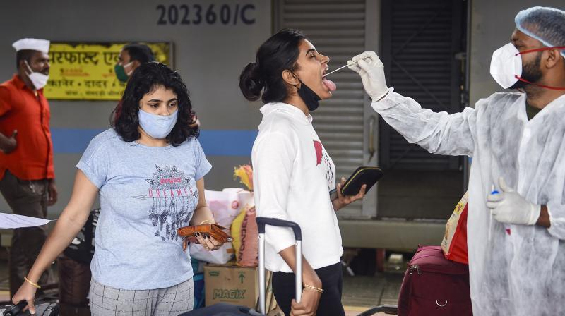 A health worker takes swab samples of a passenger for COVID-19 testing at Dadar railway station in Mumbai, Sept. 22, 2021. (PTI/Kunal Patil)