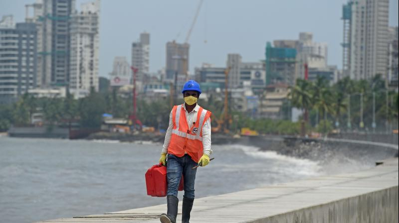 A worker walks near the construction site of a coastal road project in Mumbai . AFP Photo