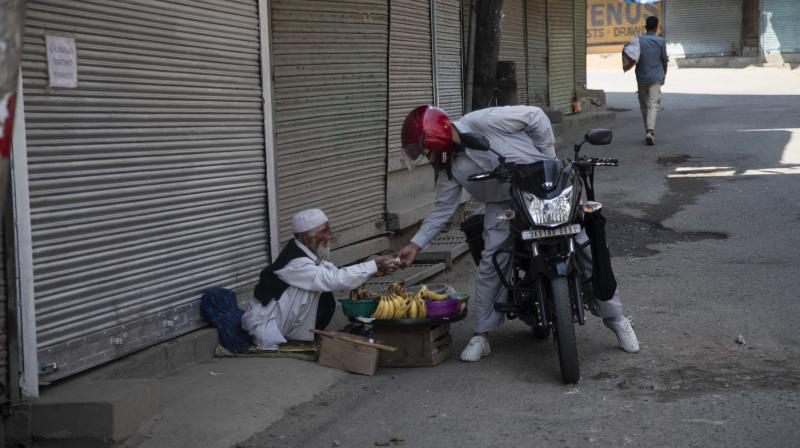 A commuter buys banana from a street vendor at a closed market during a lockdown in Srinagar. PTI Photo