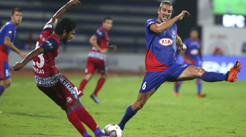 Erik Paartalu of Bengaluru FC (R) attempts to intercept a shot from Soosai Raj of Jamshedpur FC in a ISL game. AP Photo