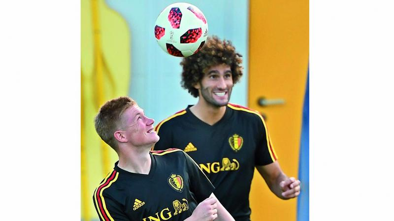 Kevin De Bruyne (left) of Belgium heads the ball next to teammate Marouane Fellaini at a training session. (Photo: AFP)