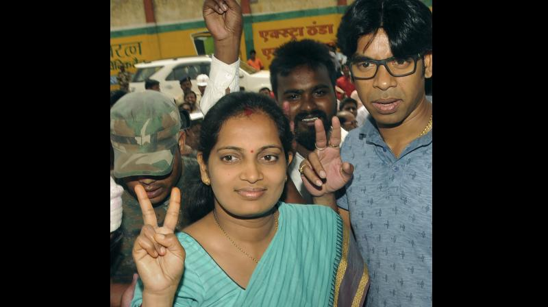 JMM candidate Seema Mahato with her husband Amit Kumar Mahato flash victory sign after winning the Silli constituency seat. (Photo: PTI)