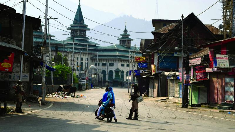 Security personnel stop a couple on a motorbike during a curfew in Srinagar on Tuesday. (Photo: AFP)