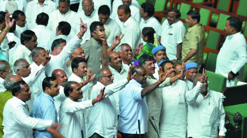 Members of the ruling party in the Karnataka Legislative Assembly show the victory sign after succesfully winning the trust vote session for the newly-sworn in chief minister of the JD(S)-Congress coalition government in the Karnataka Assembly at the Vidhana Soudha in Bengaluru on May 25. (Photo: AFP)