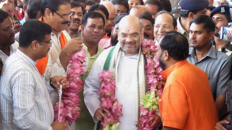 Odisha BJP President Bsanta Panda and senior leader K V Singhdeo welcome party national president Amit Shah on his arrival at the airport in Bhubaneswar. (Photo: PTI)