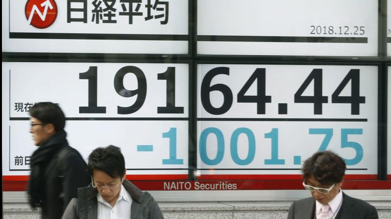 Passersby move past an electronic stock board showing the day's loss of Nikkei stock index, in front of a securities firm in Tokyo. (Photo- PTI)