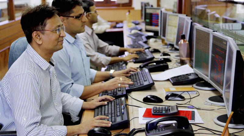 Stock brokers react to the Sensex points mark at Bombay Stock Exchange in Mumbai. (PTI Photo)