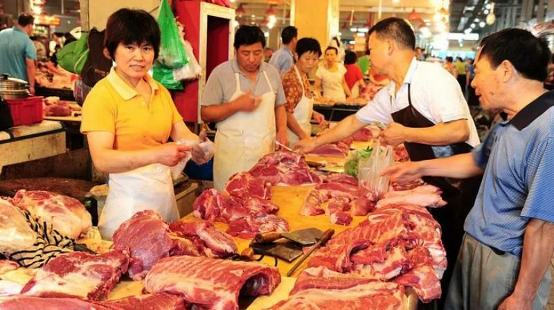 Customers shop for pork at a wet market in Taicang city, east China's Jiangsu province. (Photo- AFP)