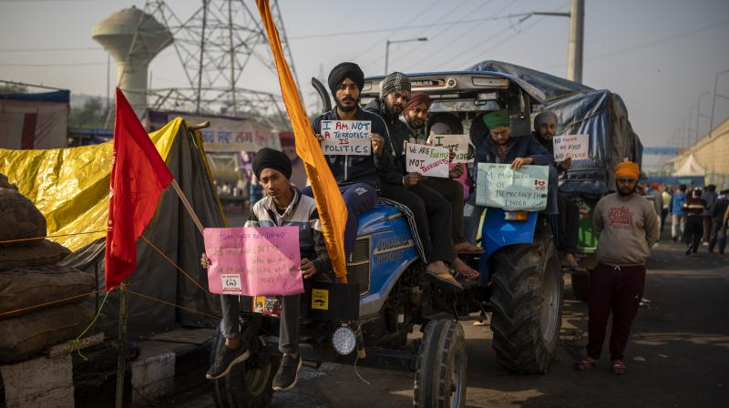 Farmers hold placards as they sit on a tractor blocking a highway in protest against new farm laws at the Delhi-Uttar Pradesh border, on the outskirts of New Delhi, India. (AP)