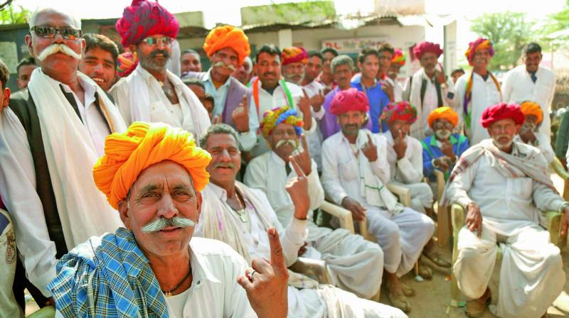 People show their fingers marked with ink after casting their vote during byelection for a parliamentary seat at a village near Ajmer. (Photo: PTI)