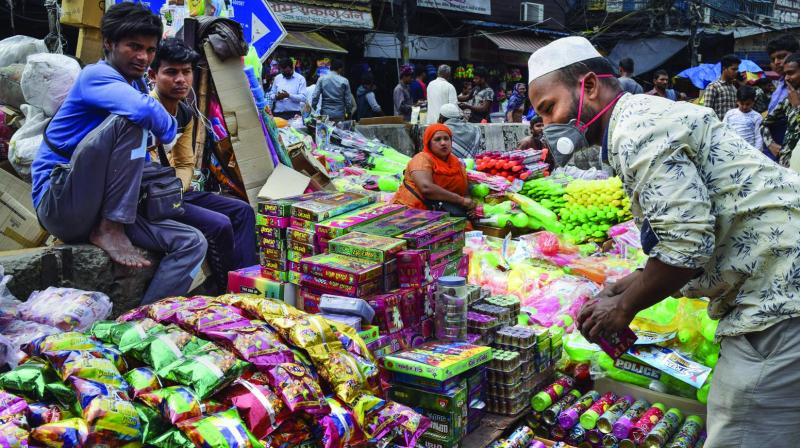 A hawker wears mask while selling Holi colours at Chandni Chowk in New Delhi on Thursday.  (Photo: PTI)