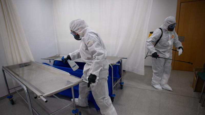A member of the Military Emergencies Unit (UME) carry out a general disinfection at the morgue of the Sant Antoni extended care facility in Barcelona. AFP Photo