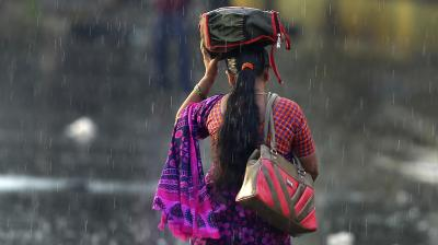 A woman walks through the rain with a bag covering her head from the downpour in the absence of an umbrella. (Photo: AP/MaheshKumar A)