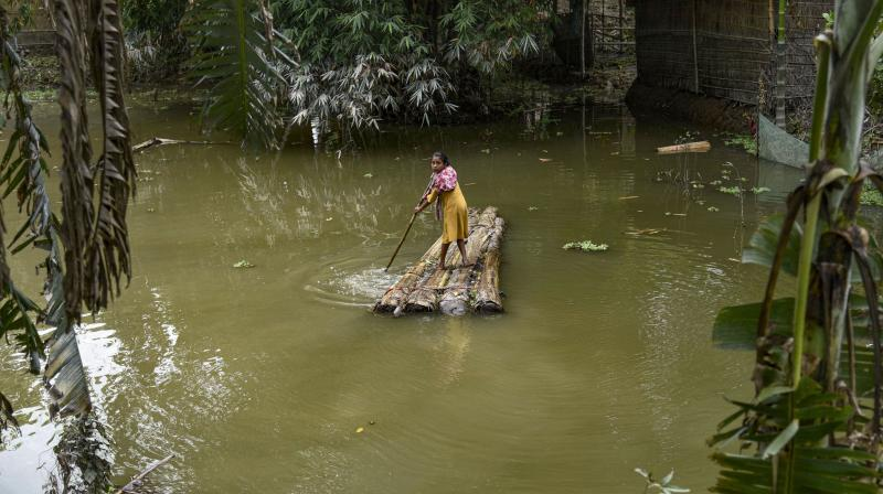 A village girl rows a makeshift raft to cross a flood-affected area in Morigaon district of Assam. PTI Photo
