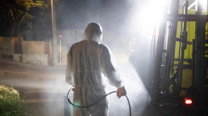 A volunteer worker carries out disinfection in Spain. AFP Photo