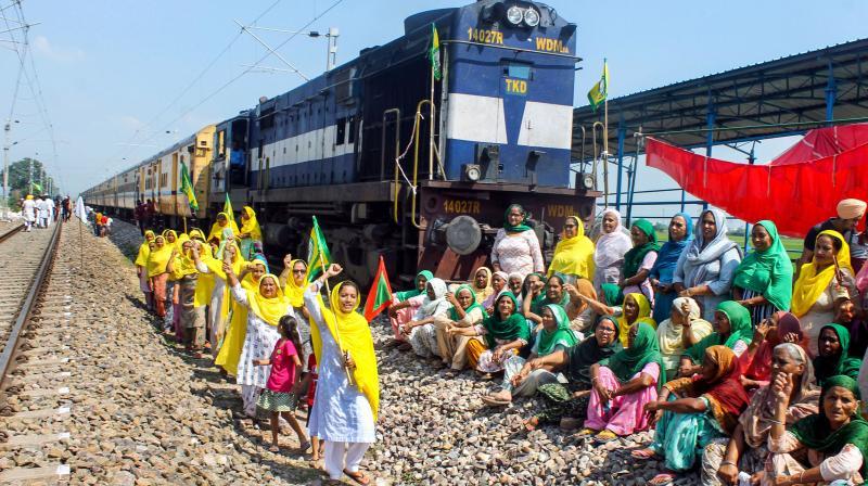 Members of Bhartiya Kisan Union Ugrahan stop the Delhi-Shri Ganganagar Intercity Express during farmers' Bharat Bandh against central government's three farm reform laws, at Daun Kalan village near Patiala, Monday, Sept. 27, 2021. (PTI)