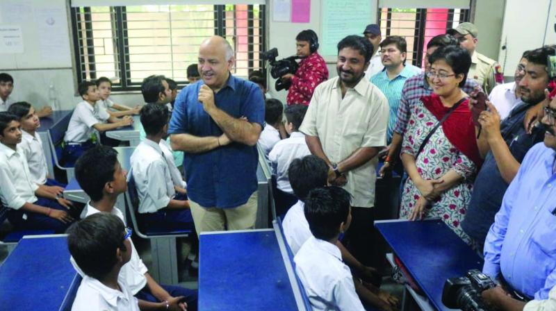 Deputy chief minister Manish Sisodia (left) with Anand Kumar (centre) and Atishi during hapiness class in a government school in New Delhi on Wednesday.