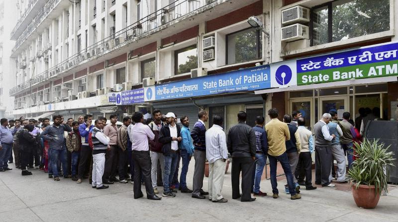 People queue up at an ATM to withdraw cash in New Delhi. (Photo: PTI)