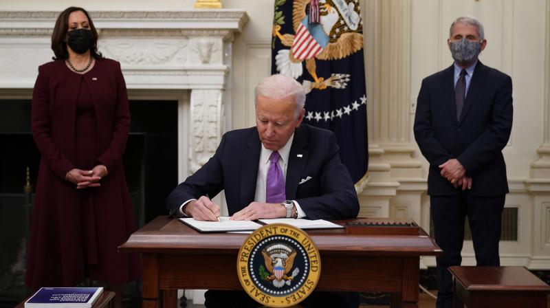US President Joe Biden signs executive orders as part of the Covid-19 response as US Vice President Kamala Harris (L) and Director of NIAID Anthony Fauci look on in the State Dining Room of the White House in Washington, DC, on January 21, 2021. (MANDEL NGAN / AFP)